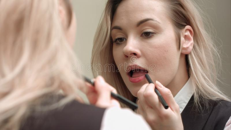 Молодая красивая женщина прикладывая красную губную помаду на ее губах стоковые изображения