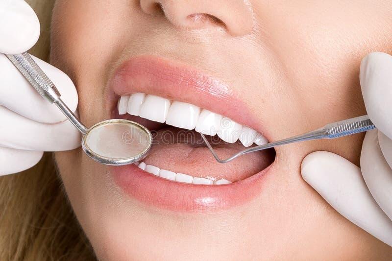 Молодая красивая женщина при красивые белые зубы сидя на зубоврачебном стуле стоковое фото