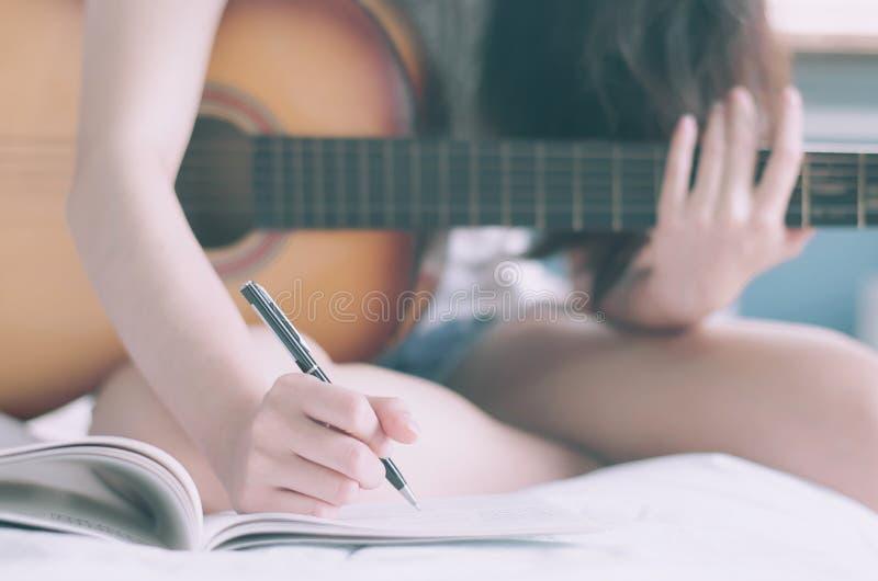 Молодая красивая женщина сидя на ее кровати в гитаре удерживания спальни составляя песню и писать песню в учебнике, музыканте, стоковое фото
