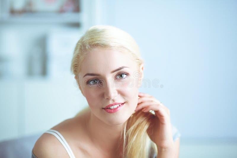 Молодая красивая женщина сидя на кресле на ее комнате стоковая фотография