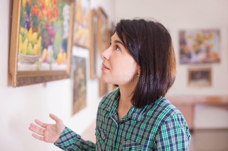Молодая красивая женщина смотря картину стоковая фотография