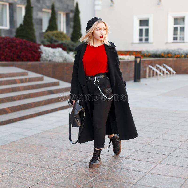 Молодая красивая женщина со светлыми волосами с кожаной сумкой в outerwear черной осени модном в стильном берете идет стоковое фото rf