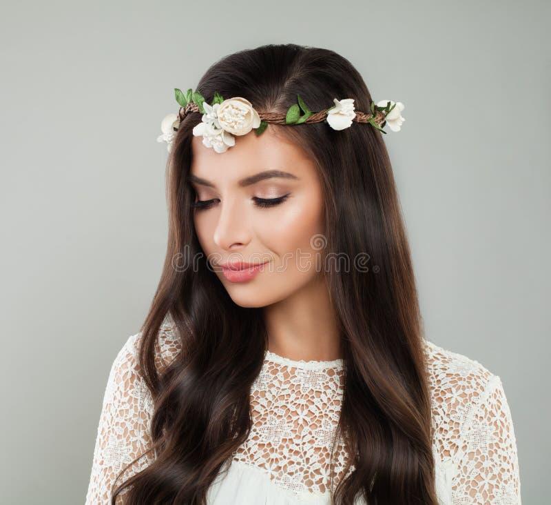 Молодая красивая женщина с белыми цветками на голове стоковая фотография