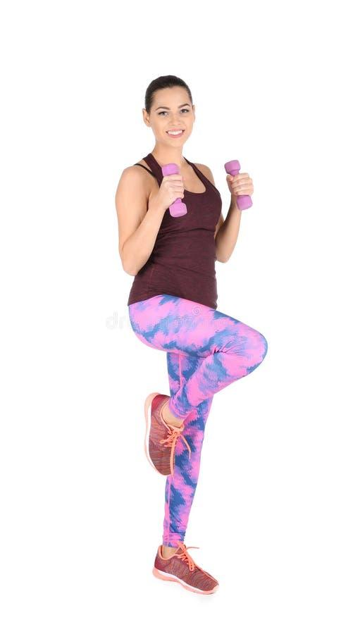 Молодая красивая женщина с гантелями делая тренировку на белизне Домашний фитнес стоковое фото