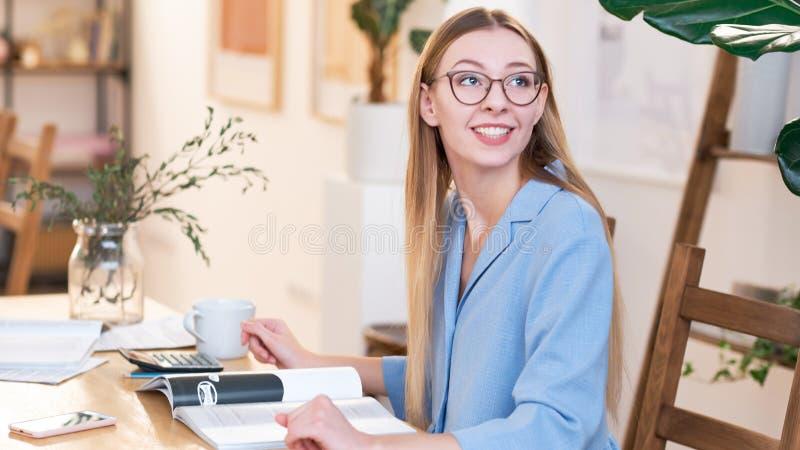 Молодая красивая женщина с длинными disheveled волосами, нося стеклами, работая в офисе, счастливая улыбка стоковые изображения rf