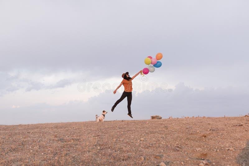 Молодая красивая женщина с ее собакой outdoors Она держит воздушные шары Влюбленность для концепции животных стоковая фотография