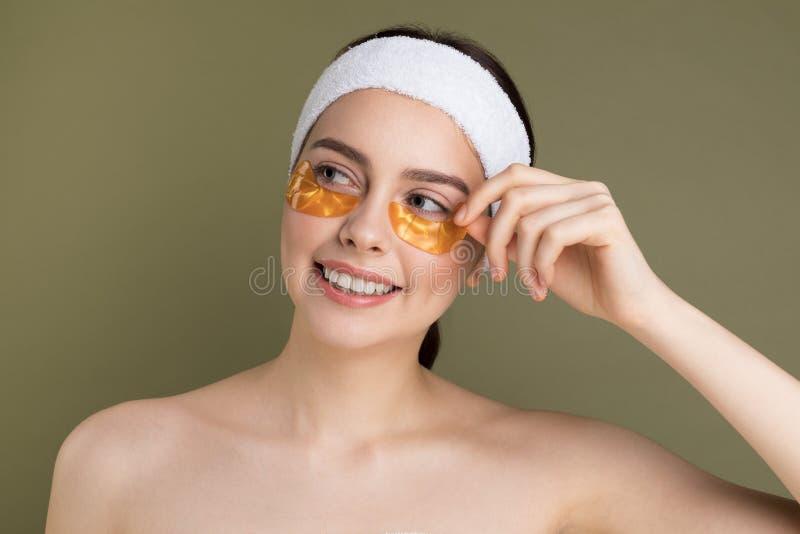 Молодая красивая женщина с естественным составляет извлекать заплату золота из-под ее глаза стоковые фото