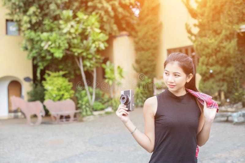 Молодая красивая женщина с ретро камерой, девушка винтажного ретро стиля азиатская на усмехаться каникул счастливый стоковое фото