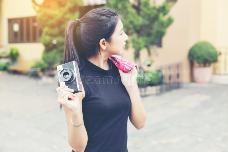 Молодая красивая женщина с ретро камерой, девушка винтажного ретро стиля азиатская на усмехаться каникул счастливый стоковая фотография