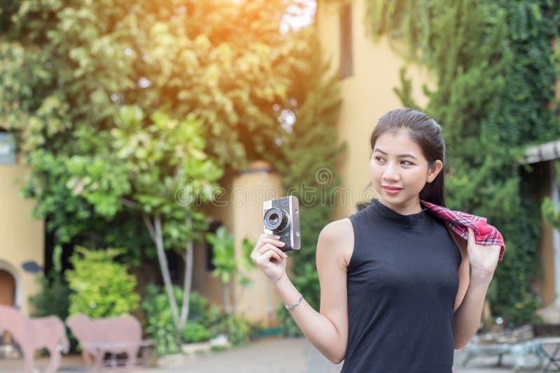 Молодая красивая женщина с ретро камерой, девушка винтажного ретро стиля азиатская на усмехаться каникул счастливый стоковое фото rf