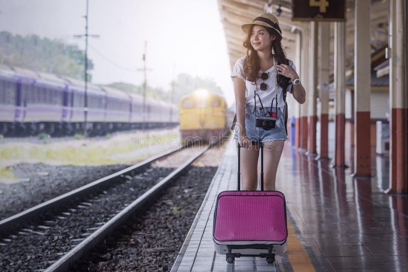 Молодая красивая женщина с розовым багажом идя на платформу железнодорожного вокзала стоковое изображение rf