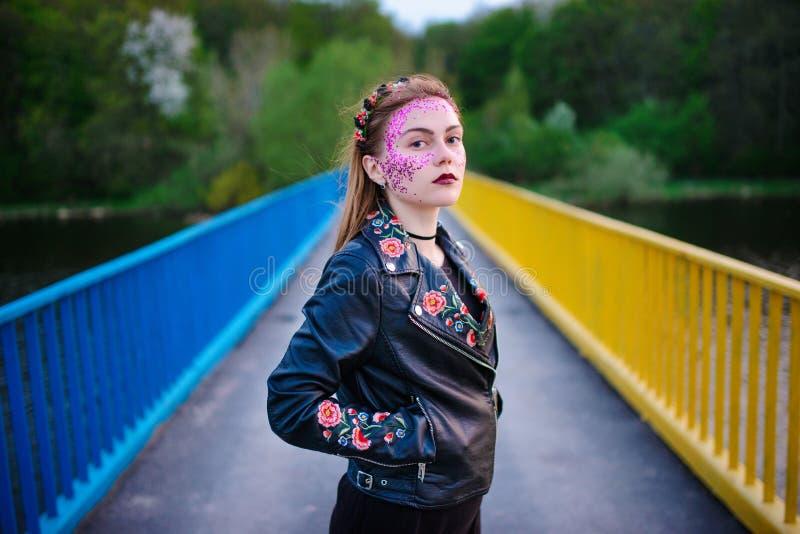 Молодая красивая женщина с фиолетовым блеском на ее стороне стоя на мосте стоковые изображения rf