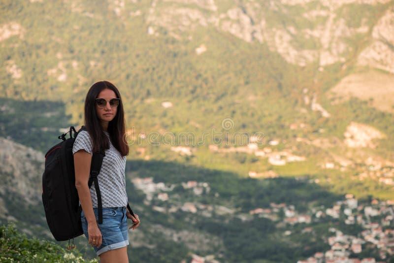 Молодая красивая женщина с черным рюкзаком путешествовать стоять на дороге Красивый молодой женский автостопщик дорогой во время  стоковое фото