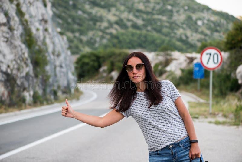 Молодая красивая женщина с черным рюкзаком путешествовать стоять на дороге Красивый молодой женский автостопщик дорогой во время  стоковая фотография rf