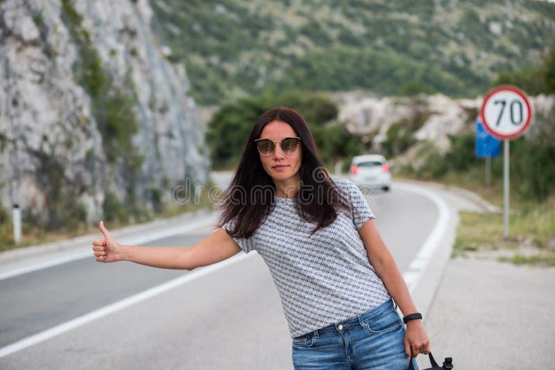Молодая красивая женщина с черным рюкзаком путешествовать стоять на дороге Красивый молодой женский автостопщик дорогой во время  стоковые изображения