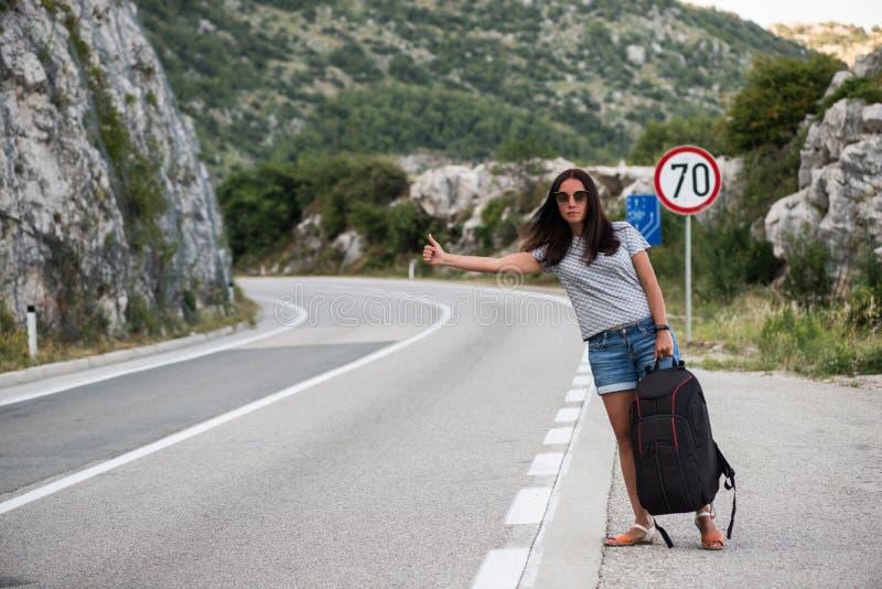 Молодая красивая женщина с черным рюкзаком путешествовать стоять на дороге Красивый молодой женский автостопщик дорогой во время  стоковые фото