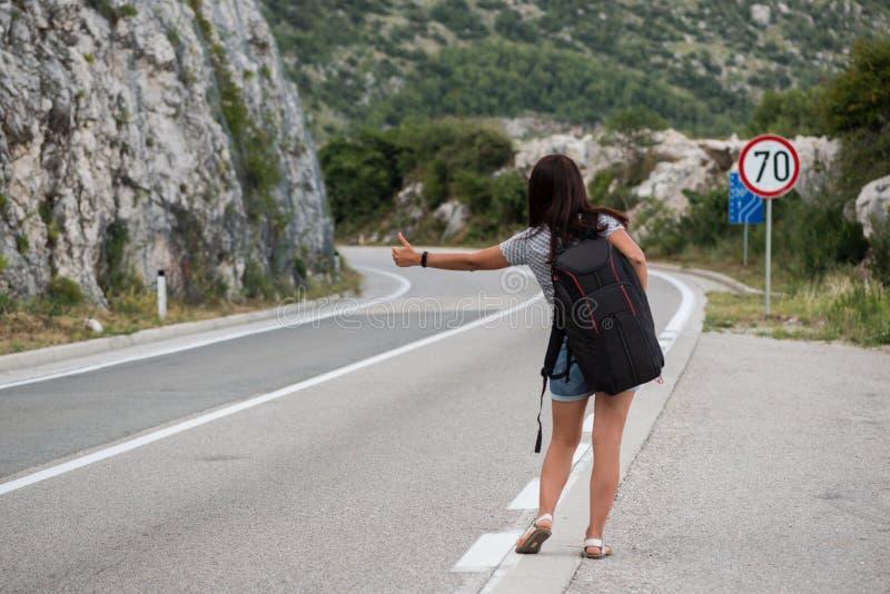 Молодая красивая женщина с черным рюкзаком путешествовать стоять на дороге Красивый молодой женский автостопщик дорогой во время  стоковое изображение rf
