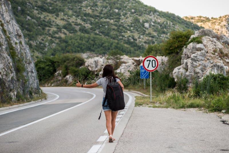 Молодая красивая женщина с черным рюкзаком путешествовать стоять на дороге Красивый молодой женский автостопщик дорогой во время  стоковое изображение