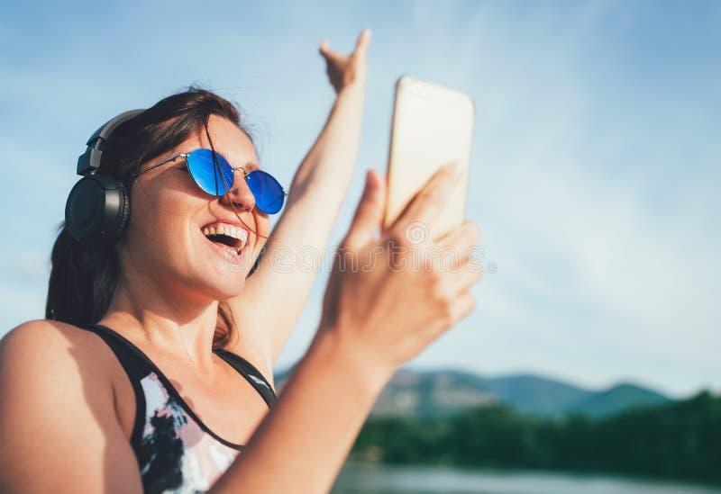 Молодая красивая женщина jogging и слушая к музыке используя смартфон и беспроводные наушники жизнерадостно усмехаясь Она поднима стоковые изображения