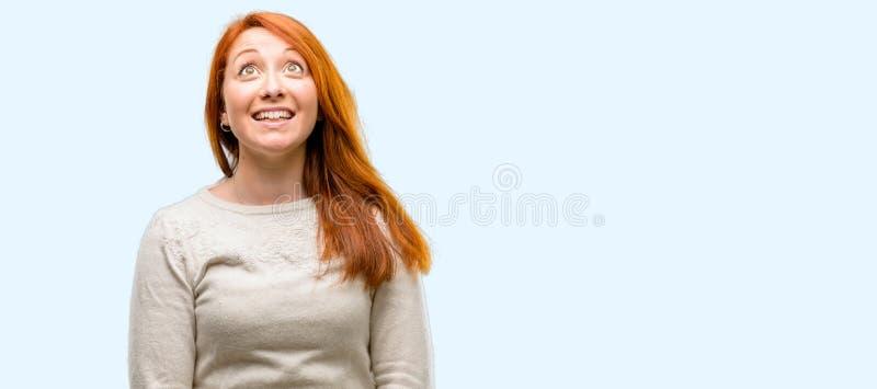 Молодая красивая женщина redhead над голубой предпосылкой стоковое изображение