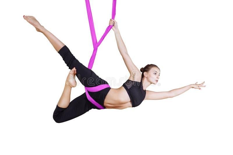 Молодая красивая женщина yogi делая воздушную практику йоги в фиолетовом гамаке на белом изоляте стоковые фото
