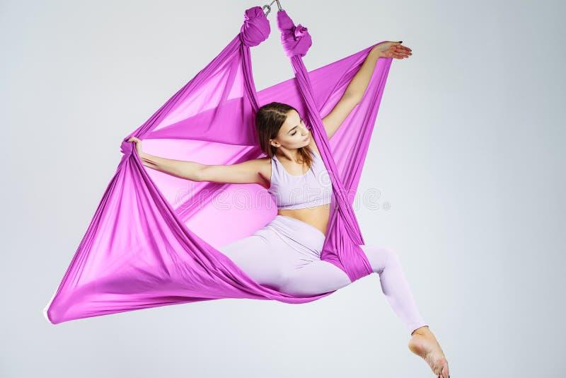 Молодая красивая женщина yogi делая воздушную практику йоги в фиолетовом гамаке стоковое фото rf