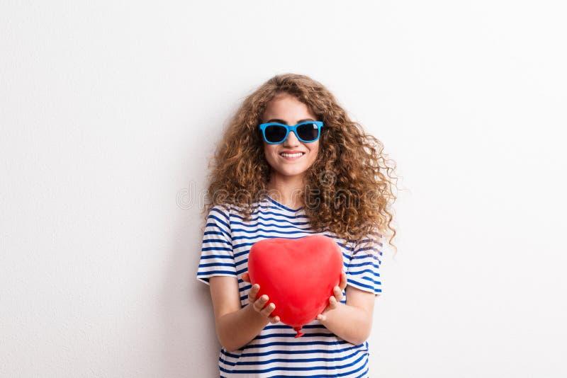 Молодая красивая жизнерадостная женщина с солнечными очками в студии, держа красное сердце стоковые изображения rf