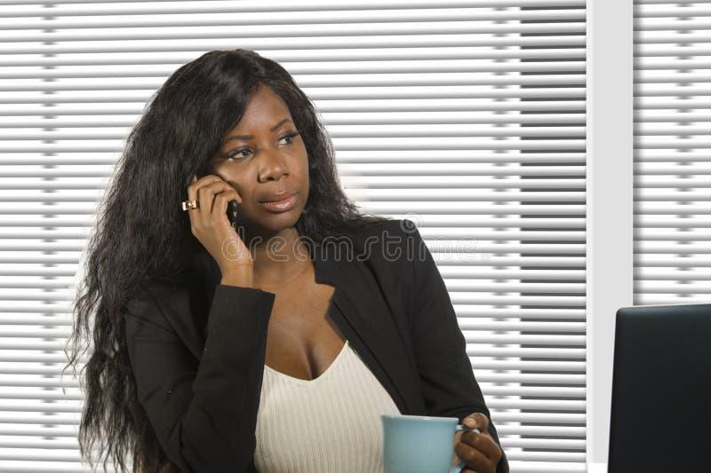 Молодая красивая и занятая черная Афро-американская коммерсантка говоря на мобильном телефоне на офисе работая с ноутбуком стоковое изображение
