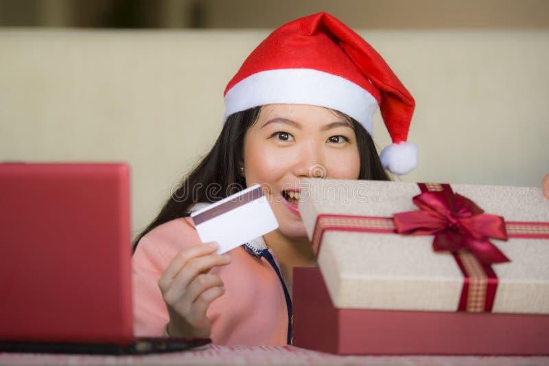 Молодая красивая и счастливая азиатская китайская женщина нося кредитную карточку удерживания шляпы Санта и коробку подарка на ро стоковое фото