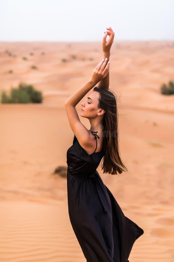Молодая красивая кавказская женщина представляя в традиционном abaya платья Emirati в пустом квартальном ландшафте пустыни стоковое изображение rf