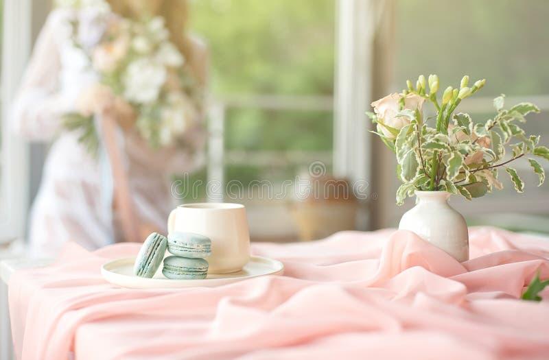 Молодая красивая кавказская невеста наслаждаясь завтраком от французских macaroon и кофе на деревянном столе с шифоновым пинком стоковое фото rf