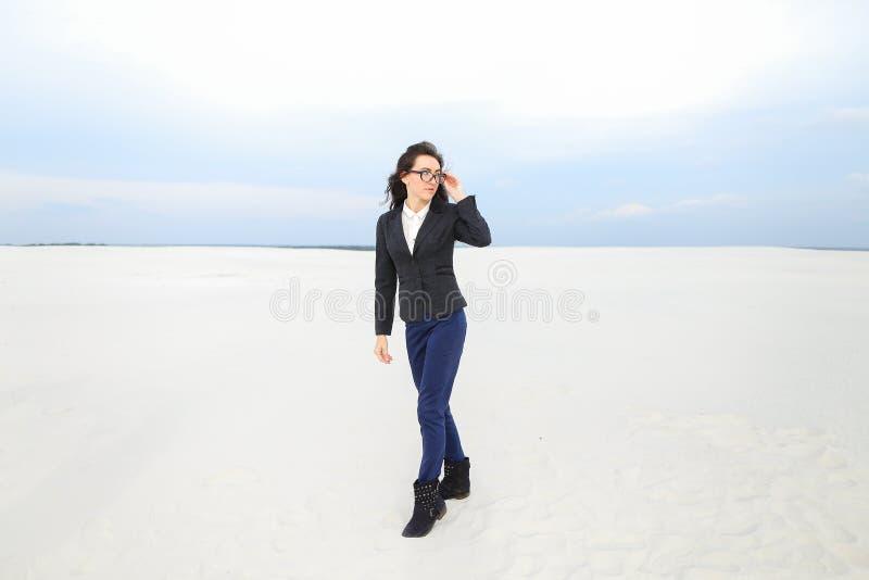 Молодая красивая коммерсантка стоя на снеге в monophonic предпосылке, нося стеклах стоковое фото