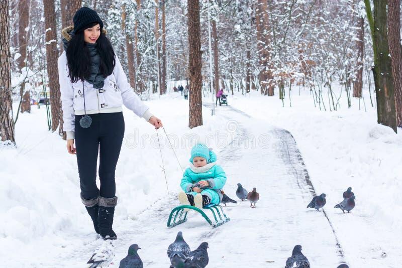 Молодая красивая мама носит ее ребенка на скелетоне в парке зимы стоковые изображения