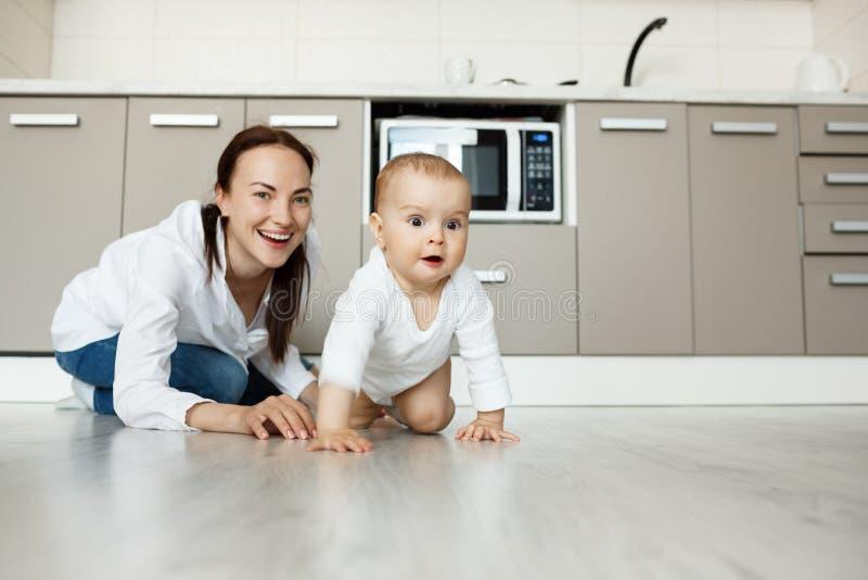Молодая красивая мать стоя на коленях в кухне играя с ее симпатичным newborn сыном Ребенок счастливо вползает в камере стоковые изображения
