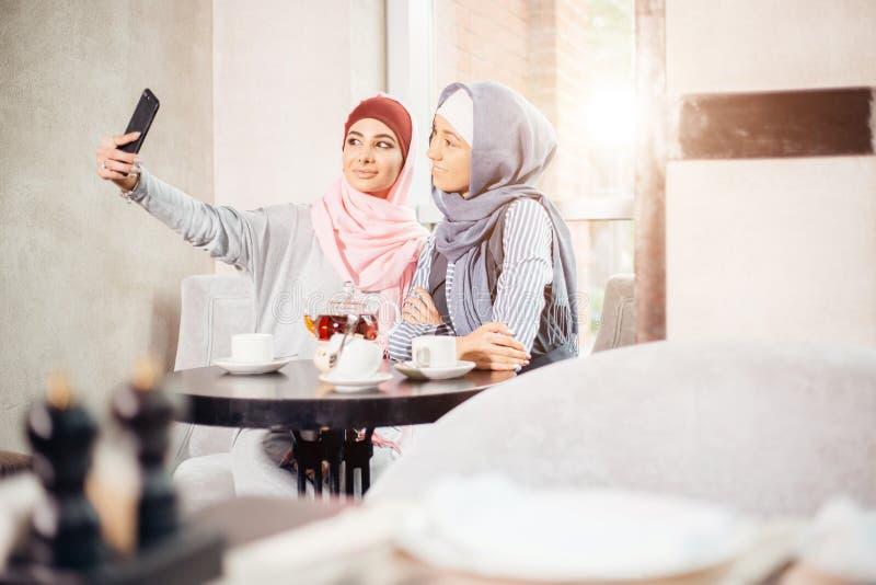 Молодая красивая мусульманская женщина принимая автопортрет с телефоном камеры стоковые фотографии rf
