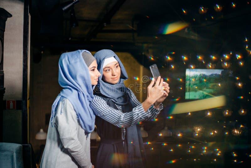 Молодая красивая мусульманская женщина принимая автопортрет с телефоном камеры стоковые фото