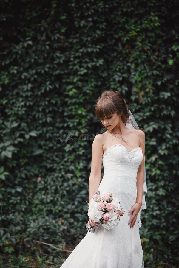 Молодая красивая невеста в элегантном платье стоит на поле около леса и держит букет стоковая фотография
