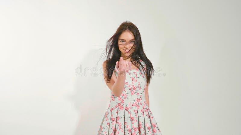Молодая красивая предназначенная для подростков девушка flirting и шаловливо приглашая соединяет к ей через палец стоковые фото