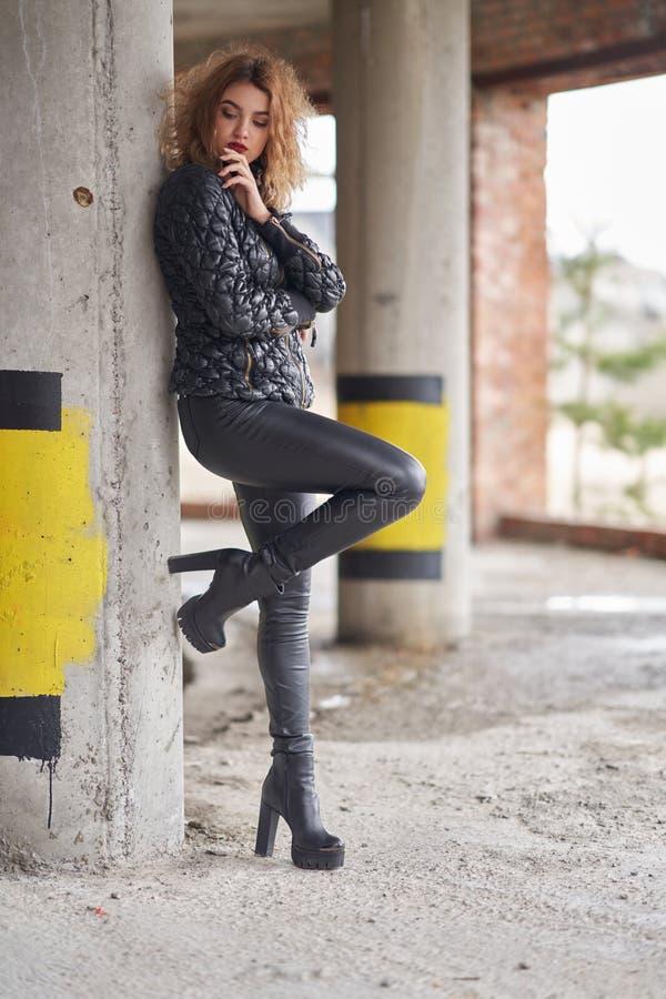 Молодая красивая рыжеволосая модная девушка в черной куртке и черных кожаных кожаных брюках, в ботинках на высокой платформе стоковые изображения rf