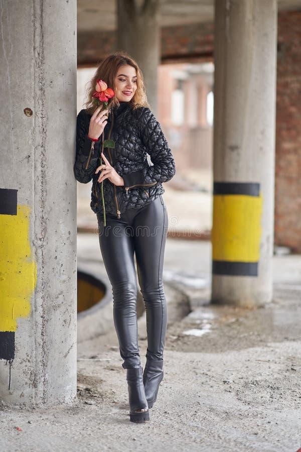 Молодая красивая рыжеволосая модная девушка с розой в ее руке в черной куртке и черных кожаных брюках стоковое изображение