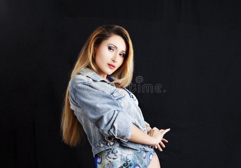 Молодая красивая сексуальная девушка представляя в куртке джинсов и модном купальнике красивейшие детеныши женщины студии съемки  стоковые фото
