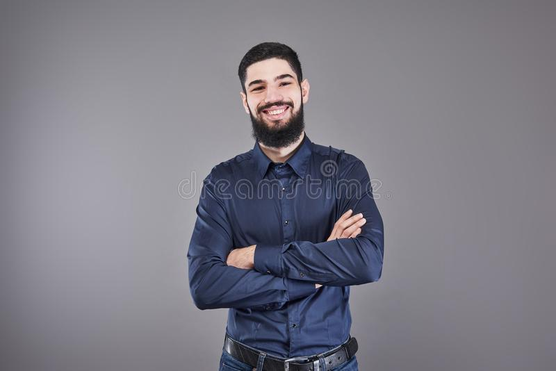 Молодая красивая склонность человека против серой стены при пересеченные оружия Серьезный молодой человек с бородой смотрит камер стоковые изображения rf