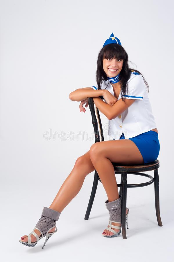 Молодая красивая стюардесса сидит на винтажном стуле стоковое изображение rf