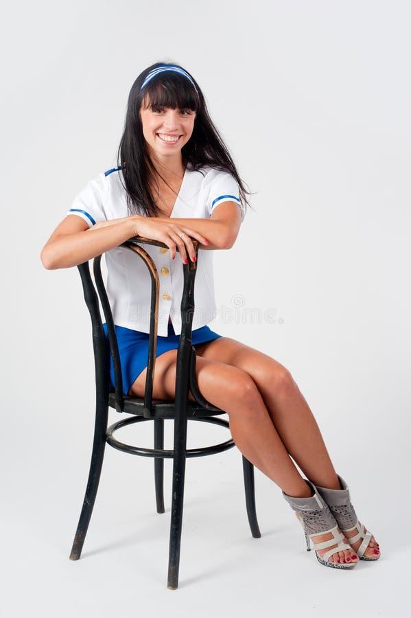 Молодая красивая стюардесса сидит на винтажном стуле стоковые фото