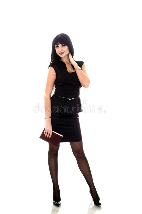 Молодая красивая счастливая женщина брюнета одетая в черном деловом костюме держа блокнот, изолированный на белом, усмехаться, см стоковое фото