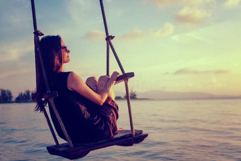 Молодая красивая счастливая женщина отбрасывая на качании на пляже во время захода солнца, ослабляя концепции образа жизни переме стоковые фото