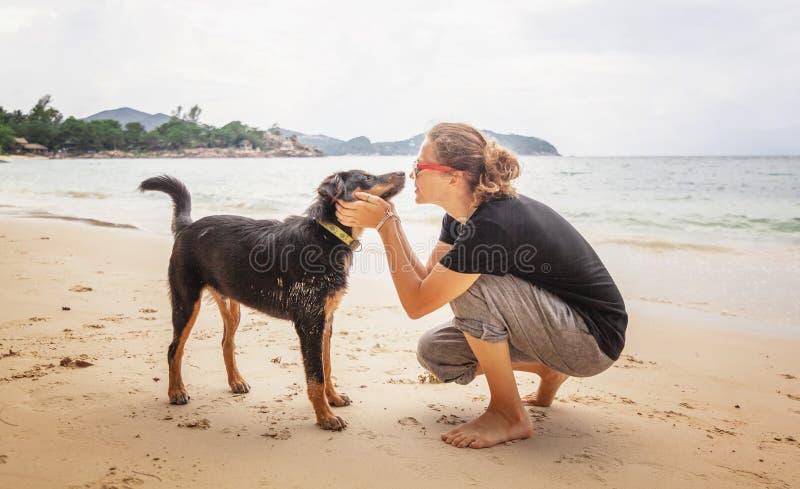 Молодая красивая счастливая радостная женщина девушки имея потеху с ее собакой на пляже босоногом в песке стоковые фотографии rf