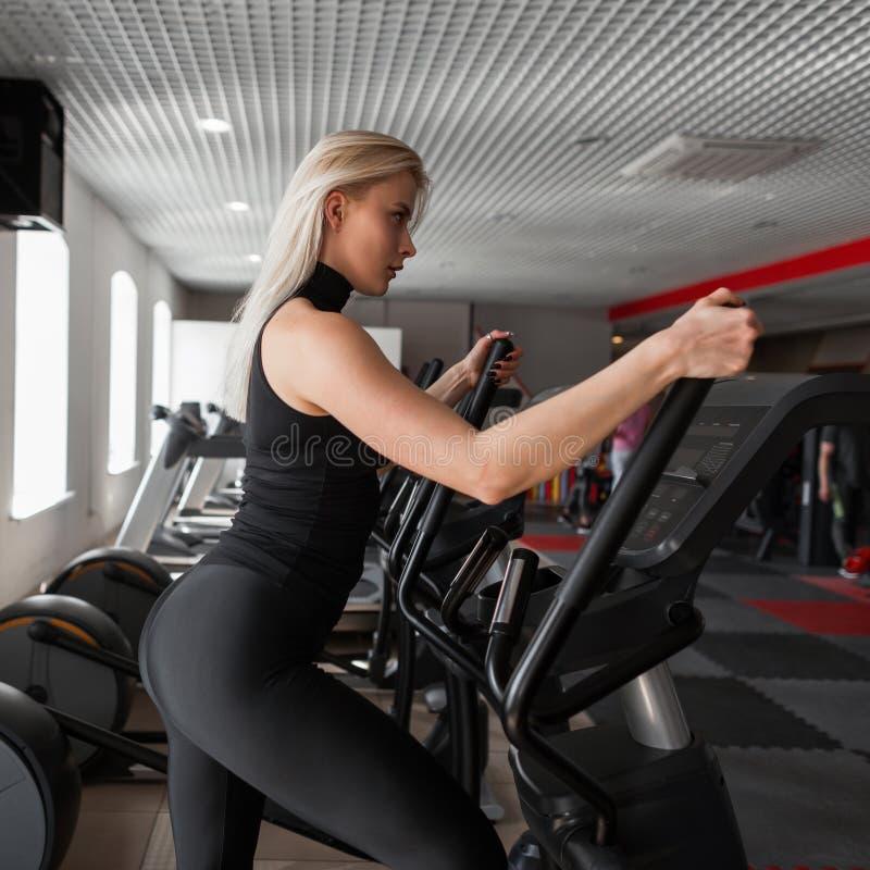 Молодая красивая тонкая женщина делая cardio тренировку на stepper имитаторе в современном спортзале Девушка в тренировке в студи стоковое фото rf