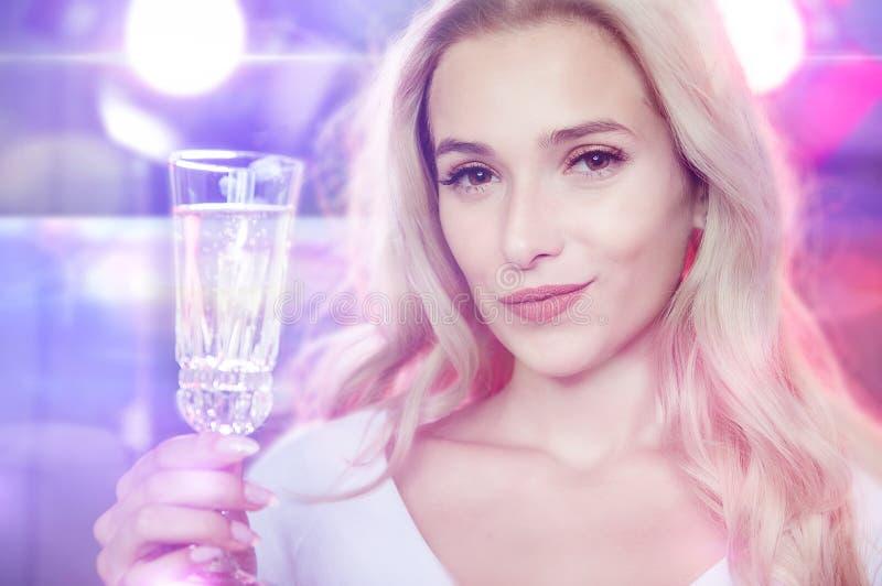 Молодая красивая усмехаясь блондинка делает здравицу стоковые изображения