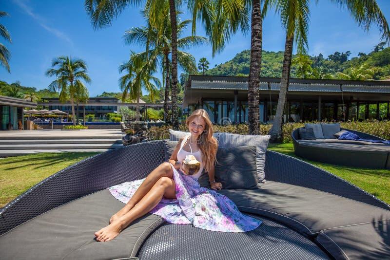 Молодая красивая усмехаясь женщина держа кокос и ослабляя стоковые фото